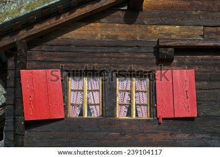 Windows with red shutters of a Swiss chalet - stock photo