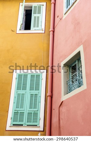 Windows with shutters on brightly coloured houses in medieval town Villefranche-sur-Mer on French Riviera, France. - stock photo