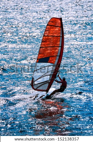 Windsurf - sailing water sports for active leisure. Surfboard with seaside in summer time. Sailboard of windsurfing in sea waves. Windsurfer in action at sea background on sunny day. - stock photo