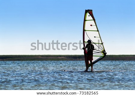 Windsurfer on the background of a coastline - stock photo