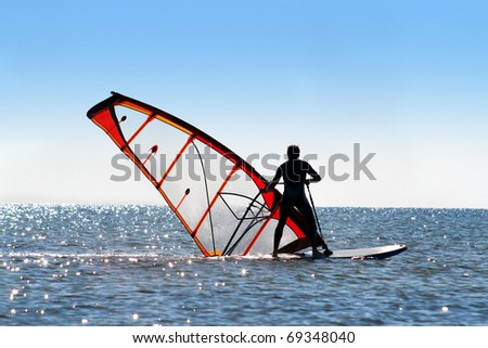 Windsurfer picks up the sail from the water surface - stock photo