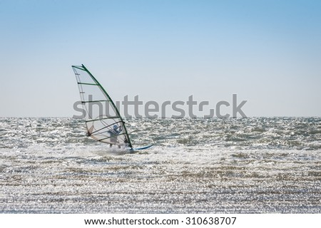 windsurfer riding the waves in an empty dea - stock photo