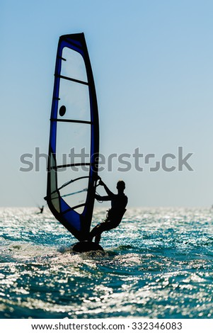 windsurfer silhouette against a sun background at the sea - stock photo