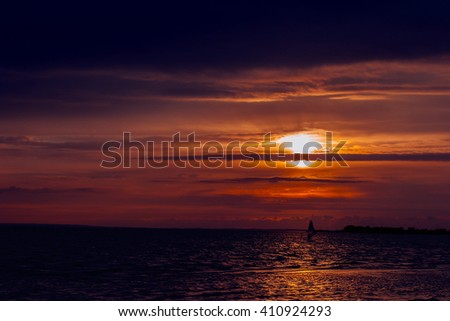 windsurfer silhouette against a sunset background at the sea - stock photo