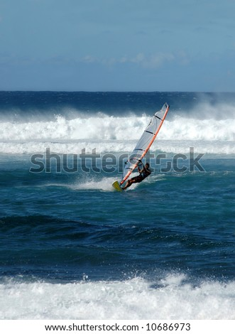 Windsurfing on the blue waters of Maui, Hawaii.   Blue water and sky. - stock photo
