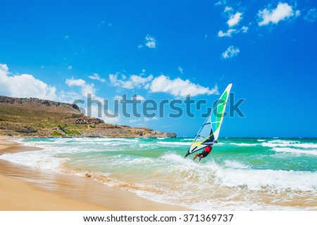 Windsurfing on the sea coast. Tropical beach with turquoise water and big waves. Crete island, Greece. - stock photo