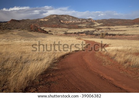 windy road in Red Mountain Open Space in northern Colorado (Larimer County), fall scenery with dry grass moved by wind - stock photo
