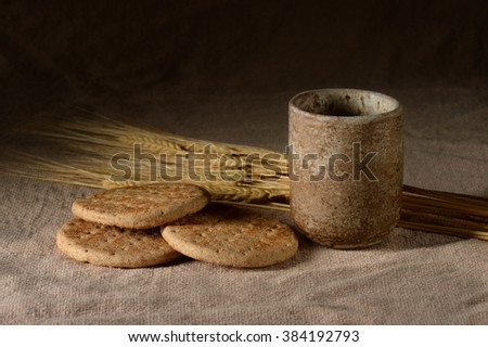 Wine and bread with wheat over vintage table cloth - stock photo