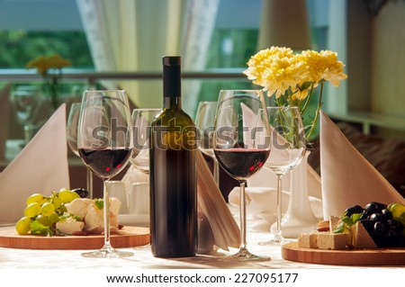Wine and grapes and cheese on the table in a restaurant - stock photo