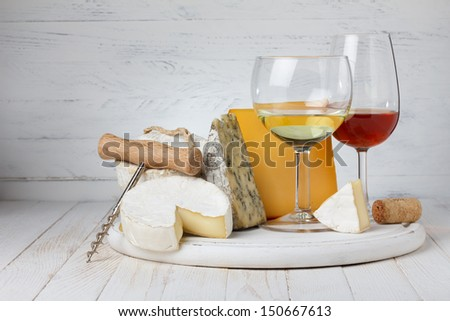 Wine and variety of cheese on wooden table still-life - stock photo