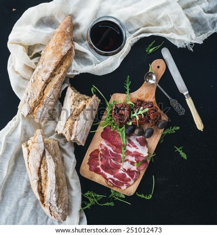 Wine appetizer set: a glass of red wine, vintage dinnerware, white towel, baguette pieces, dried tomatoes, olives, smoked meat and arugula on a rustic wooden board over a dark background. Top view  - stock photo