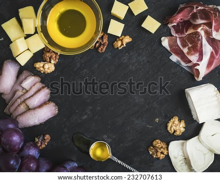 Wine appetizer set: cheese and meat selection with grapes, honey and walnuts on black stone background with a copy space in the center - stock photo