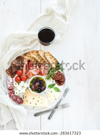 Wine appetizer set. Cherry-tomatoes, parmesan cheese, meat variety, bread slices, dried tomatoes, olives and basil on round ceramic plate over white wood backdrop, top view, copy space - stock photo
