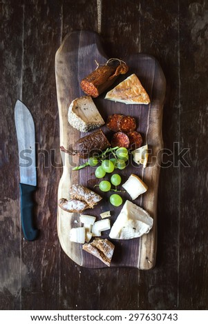 Wine appetizers set: meat and cheese selection, grapes and bread on a rustic wooden board over a dark wood background. Top view, copy space - stock photo