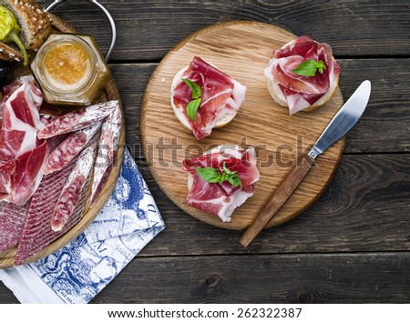 Wine appetizers set: meat and cheese selection, walnuts and olives on a dark rustic wooden background - stock photo