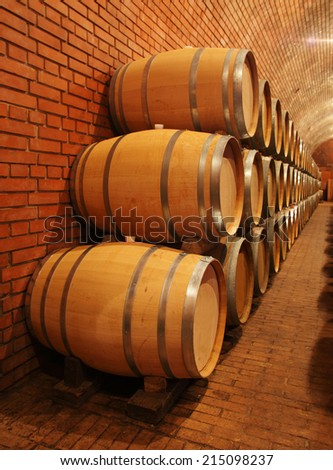 Wine barrels in wine-cellar in order - stock photo