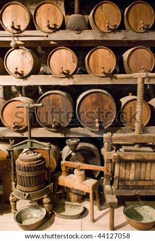 Wine barrels stacked in the old cellar of the vinery - stock photo