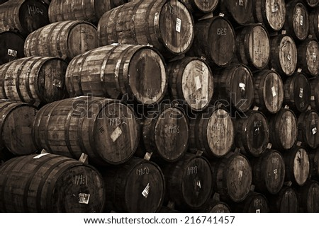 Wine barrels stacked in the old cellar of the winery. Sepia, Black and white - stock photo