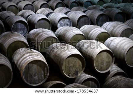 Wine barrels stacked in winery - stock photo
