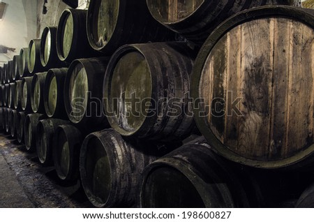 Wine barrels stacked in winery old - stock photo