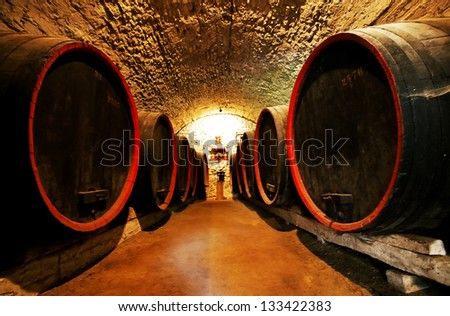 Wine barrels stacked into an old cellar of the winery - stock photo