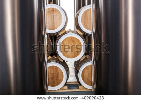 Wine barrels stacked near metal tanks in the winery - stock photo