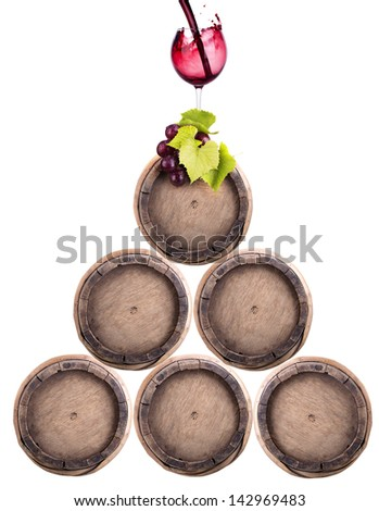 Wine barrels with grapevine and glass in pyramid isolated - stock photo