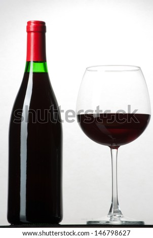 Wine bottle and a glass filled with wine isolated on white - stock photo