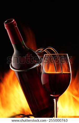 Wine bottle and glass with a fire on a black background - stock photo