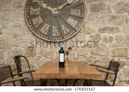 Wine bottle and two glasses on the wooden table decorated with rose. - stock photo