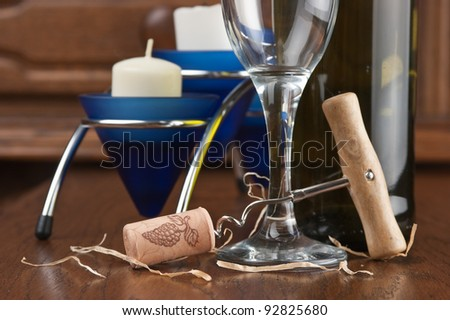 wine bottle and wineglass on a wooden table - stock photo