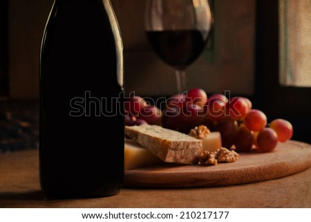 Wine bottle, glass and cheese plate. Very soft focus effect toned vintage paper. - stock photo
