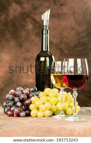 Wine bottle near shiny wine cups and grape - stock photo