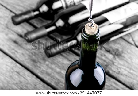 Wine bottle on a wooden table standing out from the crowd - stock photo