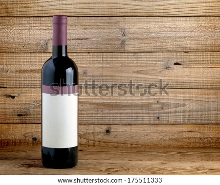 Wine bottle on wooden background - stock photo