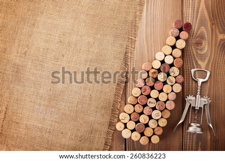 Wine bottle shaped corks and corkscrew over rustic wooden table background and burlap. Top view with copy space  - stock photo