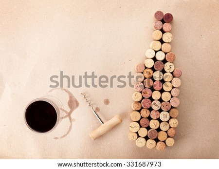 Wine bottle shaped corks, glass of wine and corkscrew over cardboard paper background. View from above with copy space - stock photo