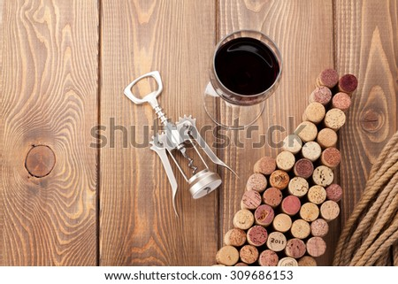 Wine bottle shaped corks, glass of wine and corkscrew over rustic wooden table background. View from above with copy space - stock photo