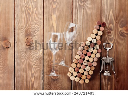 Wine bottle shaped corks, glasses and corkscrew over rustic wooden table background. View from above with copy space - stock photo