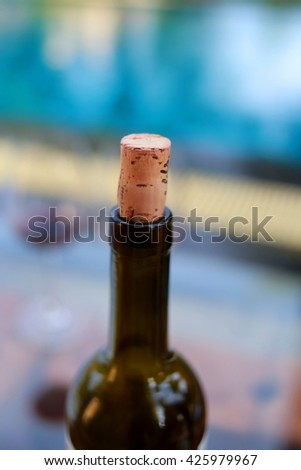 Wine bottle stopper beside the pool. - stock photo