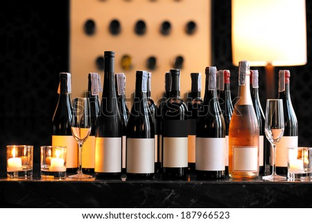 Wine bottle with candle and empty wine glasses on counter bar - stock photo