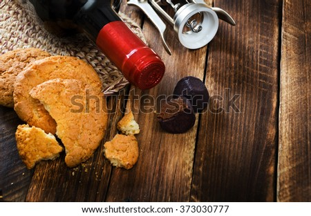 wine bottle with cookies and chocolate on wooden table - stock photo