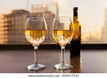 Wine bottle with glasses against city view. - stock photo