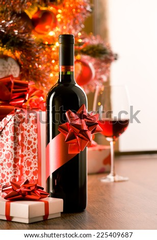 Wine bottle with red ribbon with christmas gift boxes and tree on background. - stock photo