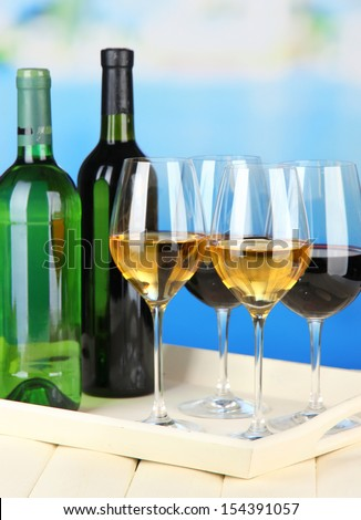 Wine bottles and glasses of wine on tray, on bright background - stock photo