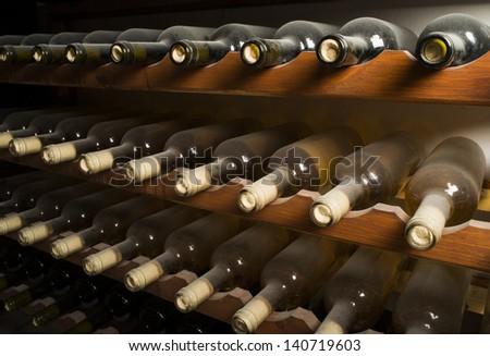 Wine bottles on shelf. Wine cellar. Close up wine bottles. - stock photo