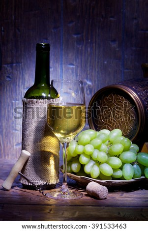 Wine bottles, small barrel,  bunch of grapes and glass of white wine on blue old wooden background - stock photo