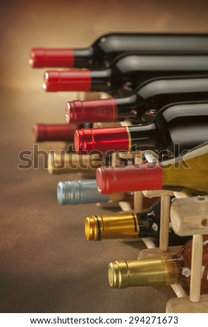 wine bottles stacked on wooden racks shot vertically with limited depth of field - stock photo
