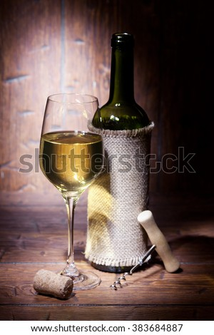 Wine bottles with glass of white wine on old wooden background - stock photo