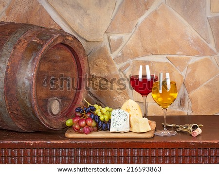 Wine, cheese, grapes and old wooden barrel with iron rings; still life - stock photo